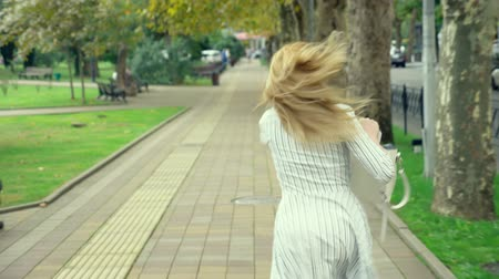 késő : woman blonde is talking on the phone on the run, she is in a hurry. outdoors in summer. slow-motion