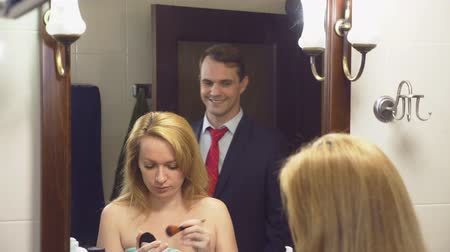 várjon : couple, husband and wife gather in the bathroom. the husband already dressed is waiting for his un-assembled wife. 4k, slow motion