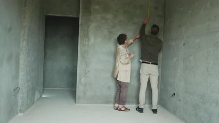 inquiry : settlers inspect the room in a rough finish. construction, home buying Stock Footage