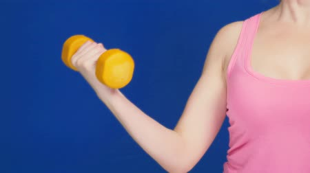 болваны : A woman in a pink T-shirt with a deep neckline does a dumbbell bench press. Exercise for biceps. copy space Стоковые видеозаписи