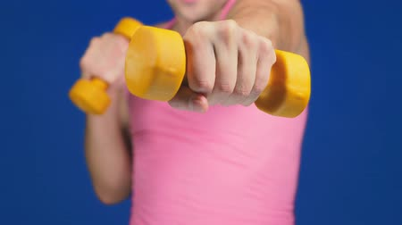 aerobic : A man in a pink T-shirt with a deep neckline is boxing dumbbells. focus on dumbbells, body blurry. copy space