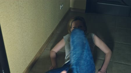 savage : horror, a girl crawls away from her investigator, falling to the floor in the corridor of her house.