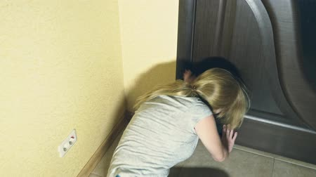 megváltás : horror, a girl crawls away from her investigator, falling to the floor in the corridor of her house.