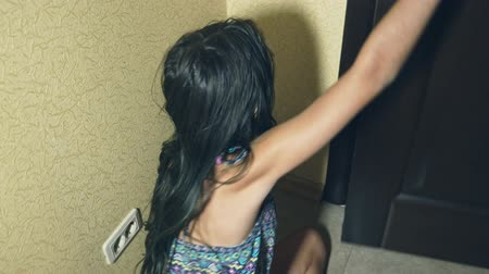 teror : horror, a girl crawls away from her investigator, falling to the floor in the corridor of her house.