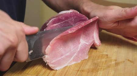 kasap : man cuts raw frozen meat with a knife in slow motion. 4k close-up