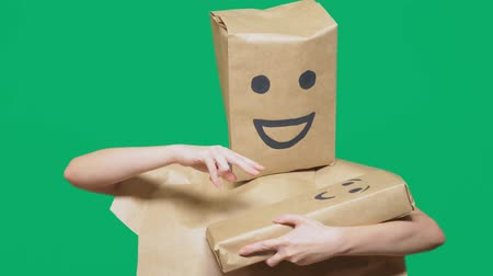 aç : concept of emotions, gestures. man with a package on his head, with a painted emoticon, smile, joy, laughter. plays with the child painted on the box.