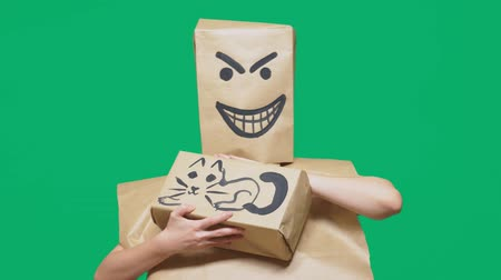 öfkeli : concept of emotion, gestures. a man with a package on his head, with a painted smiley angry, sly, gloating and stroking a cat painted on a box.