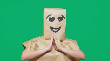 bilinmeyen : concept of emotions, gestures. a man with paper bags on his head, with a painted emoticon, smile, joy, love eyes. Stok Video