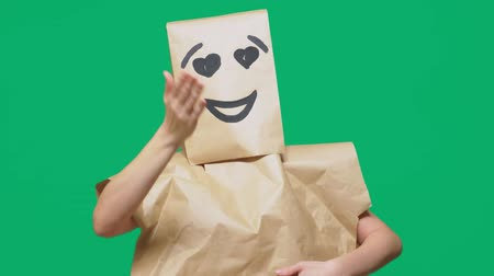 контейнеры : concept of emotions, gestures. a man with paper bags on his head, with a painted emoticon, smile, joy, love eyes. Стоковые видеозаписи