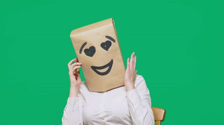 aç : concept of emotions, gestures. a man with paper bags on his head, with a painted emoticon, smile, joy, love. talking on a cell phone Stok Video
