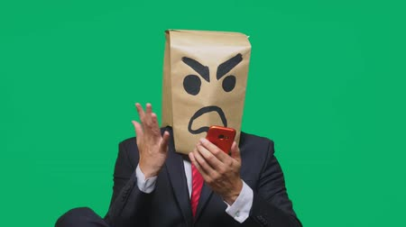 demons : concept of emotion, gestures. a man with a package on his head, with a painted smiley aggressive, angry. talking on a cell phone Stock Footage