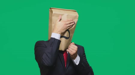 dread : concept of emotions, gestures. a man with paper bags on his head, with a painted emoticon, fear. Stock Footage