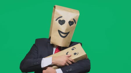 aç : concept of emotions, gestures. a man with a package on his head, with a painted emoticon, smile, enamored eyes. plays with the child painted on the box.