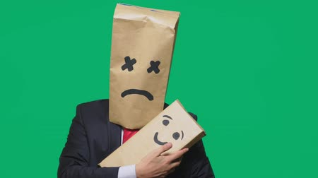 risonho : concept of emotions, gestures. a man with a package on his head, with a painted emoticon, tired, sleepy. plays with the child painted on the box. Vídeos