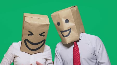 bizarre : concept of emotions, gestures. a couple of people with bags on their heads, with a painted emoticon, smile, joy, laugh.