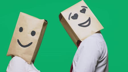 aç : concept of emotions, gestures. a couple of people with paper bags on their heads, with a painted emoticon, smile, joy, eyes in love.
