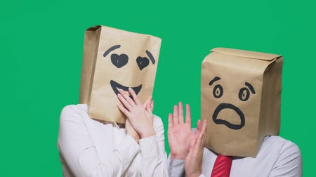 bizarre : concept of emotions, gestures. a couple of people with bags on their heads, with a painted emoticon, a smile, eyes in love, and the second with a mask of fright, fear. sexual harassment concept