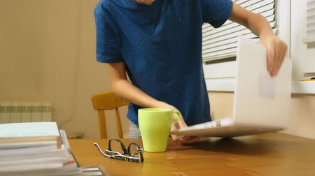 kořist : boy teenager poured tea on the laptop. doing homework, online learning, 4k close-ups,