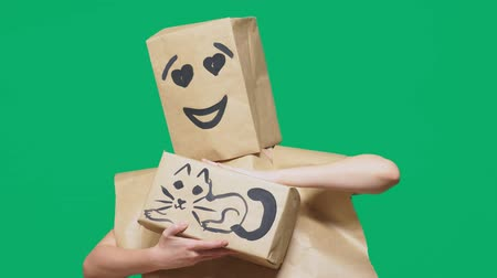 aç : concept of emotions, gestures. a man with a package on his head, with a painted emoticon, smile, loving eyes. plays with a cat drawn on the box. Stok Video