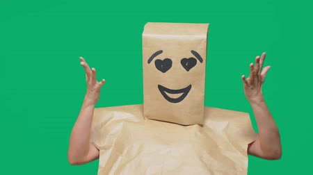 aç : concept of emotions, gestures. a man with paper bags on his head, with a painted emoticon, smile, joy, love eyes. Stok Video