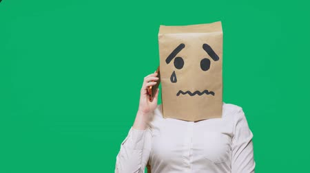 estranho : concept of emotion, gestures. a man with a package on his head, with a painted smiley crying, sad, talking on the phone Vídeos
