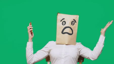 dread : concept of emotions, gestures. a man with paper bags on his head, with a painted emoticon, fear. talking on a cell phone