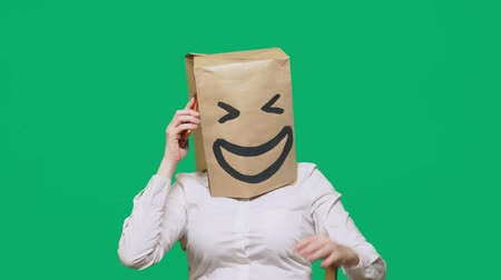 bizarre : concept of emotions, gestures. a man with paper bags on his head, with a painted emoticon, smile, joy. talking on a cell phone