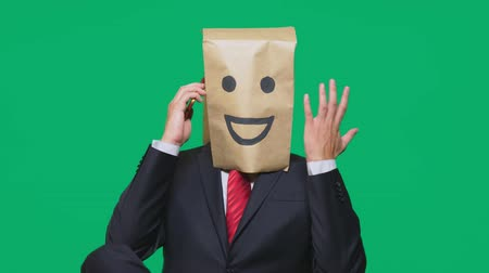anonymní : concept of emotions, gestures. a man with paper bags on his head, with a painted emoticon, smile, joy. talking on a cell phone