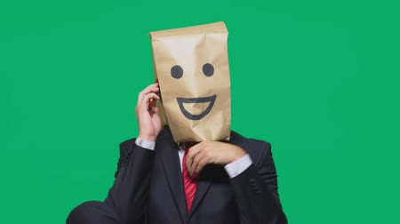 aç : concept of emotions, gestures. a man with paper bags on his head, with a painted emoticon, smile, joy. talking on a cell phone