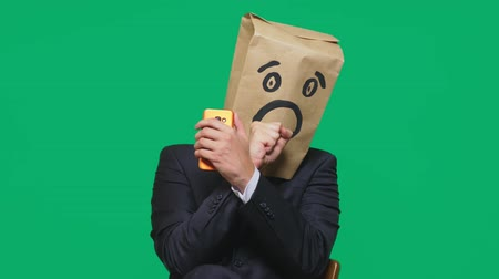bizarre : concept of emotions, gestures. a man with paper bags on his head, with a painted emoticon, fear. talking on a cell phone