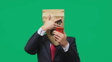 teror : concept of emotions, gestures. a man with paper bags on his head, with a painted emoticon, fear. talking on a cell phone