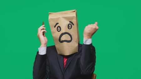 anonymní : concept of emotions, gestures. a man with paper bags on his head, with a painted emoticon, fear. talking on a cell phone