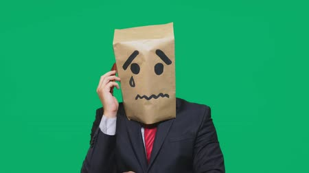 странный : concept of emotion, gestures. a man with a package on his head, with a painted smiley crying, sad, talking on the phone Стоковые видеозаписи