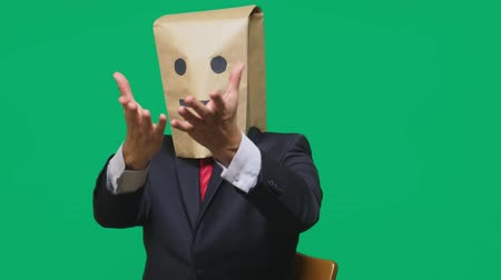anonymní : concept of emotions, gestures. a man with paper bags on his head, with a painted emoticon, smile, joy