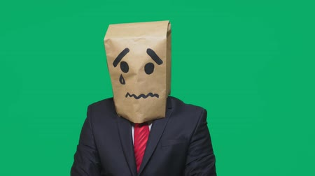 странный : concept of emotion, gestures. a man with a package on his head, with a painted smiley crying, sad