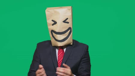 aç : concept of emotions, gestures. a man with paper bags on his head, with a painted emoticon, smile, joy