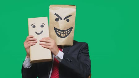 bizarre : concept of emotions, gestures. a man with a package on his head, with a painted emoticon devil, crafty, gloating. plays with the child drawn on the box. childs deception, naivety