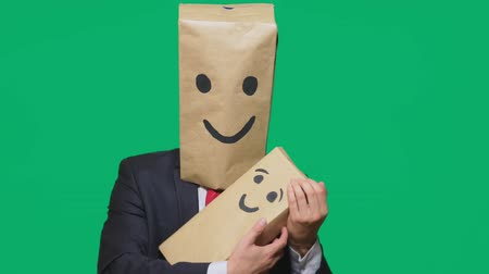 unknown : concept of emotions, gestures. man with a package on his head, with a painted emoticon, smile, joy, laughter. plays with the child painted on the box.