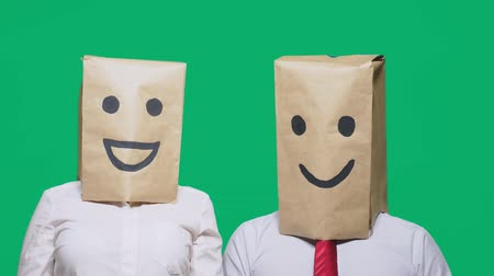 pintado : concept of emotions, gestures. a couple of people with bags on their heads, with a painted emoticon, smile, joy, laugh.