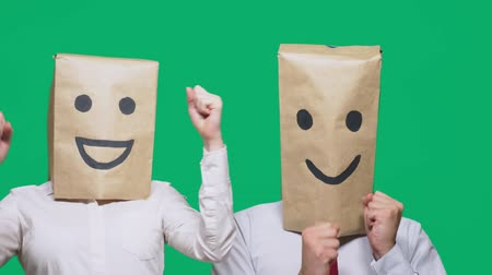aç : concept of emotions, gestures. a couple of people with bags on their heads, with a painted emoticon, smile, joy, laugh.
