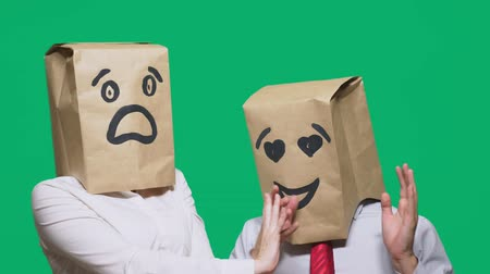 nádoba : concept of emotions, gestures. a couple of people with bags on their heads, with a painted emoticon, a smile, eyes in love, and the second with a mask of fright, fear. sexual harassment concept