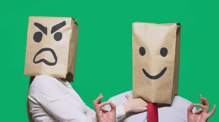 bizarre : The concept of emotions and gestures. Two people in paper bags on the head with painted smileys. Aggressive smiley swears. The second smiles at him.