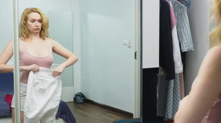 gidermek : Clothing, wardrobe, fashion, style and concept of people. puzzled blonde makes a choice of clothes, standing near the closet and looking at herself in the mirror