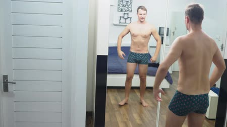 üstsüz : Young man checking his muscles in front of a mirror in the bedroom Stok Video