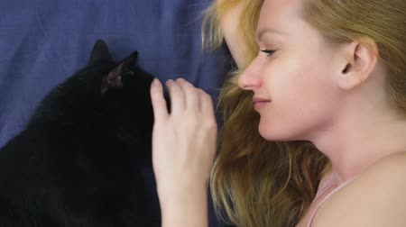 arranhão : Girl with a cat. Beautiful blonde girl lying in bed and caressing her black cat. Caring for animals. love for pets