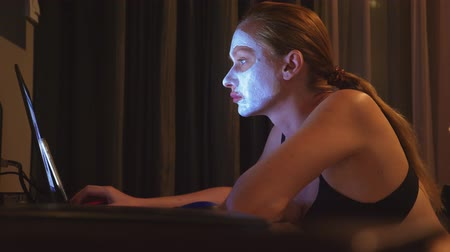 clay mask : young woman with cosmetic mask on face working with laptop at home in the evening. naturalness