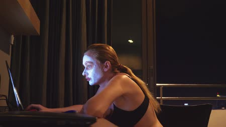 anti : young woman with cosmetic mask on face working with laptop at home in the evening. naturalness