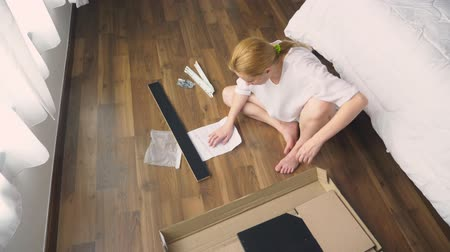 settings : Assembling furniture at home, a housewife assembles a computer desk using hand tools. Stock Footage