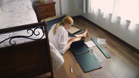 vidalar : Assembling furniture at home, a housewife assembles a computer desk using hand tools. Stok Video