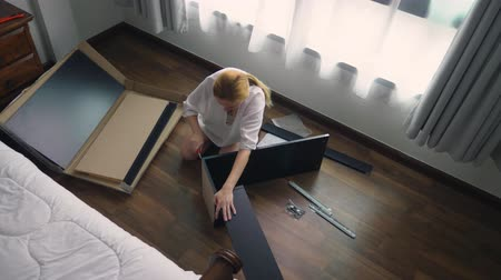 bracket : Assembling furniture at home, a housewife assembles a computer desk using hand tools. Stock Footage